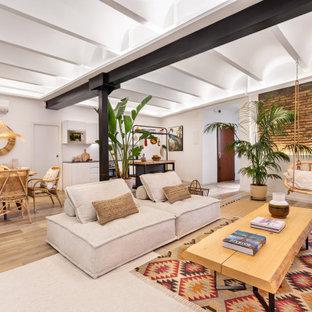 Imagen de sala de estar con barra de bar tipo loft y ladrillo, exótica, grande, sin chimenea, con paredes azules, suelo de madera clara, televisor independiente, suelo beige y ladrillo