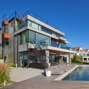 Ejemplo de fachada de casa moderna, grande, de tres plantas, con revestimiento de hormigón, tejado plano y techo verde