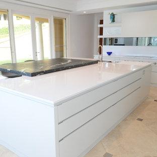 シドニーの大きいコンテンポラリースタイルのおしゃれなキッチン (ダブルシンク、フラットパネル扉のキャビネット、白いキャビネット、大理石カウンター、白いキッチンパネル、ミラータイルのキッチンパネル、シルバーの調理設備の、トラバーチンの床) の写真