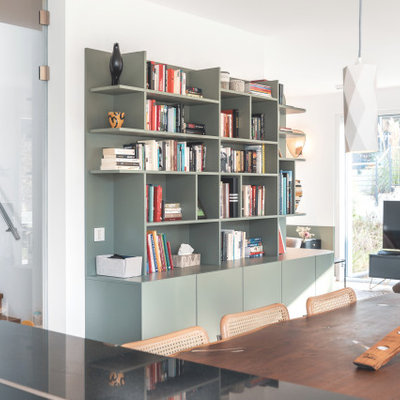 Family room library - large eclectic open concept painted wood floor family room library idea in Nuremberg with a wood stove