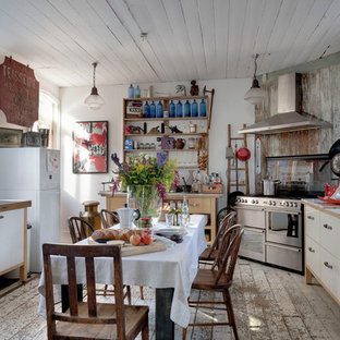This is an example of a traditional u-shaped eat-in kitchen in Kent with flat-panel cabinets, white cabinets, stainless steel appliances and painted wood floors.