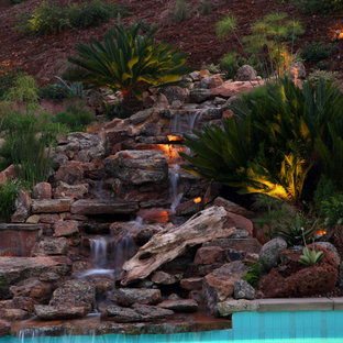 This is an example of a large rustic full sun backyard stone waterfall in San Diego.