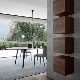 Imagen de comedor actual, grande, abierto, sin chimenea, con paredes grises, suelo de madera en tonos medios, marco de chimenea de hormigón y suelo marrón