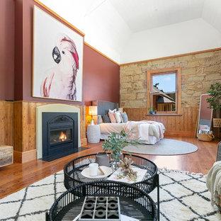 Esempio di un'ampia camera degli ospiti contemporanea con pareti viola, parquet chiaro, stufa a legna e cornice del camino in metallo