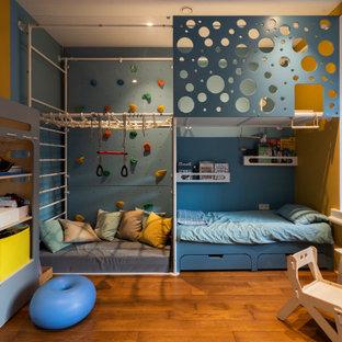 Idéer för ett mellanstort industriellt småbarnsrum kombinerat med lekrum, med vita väggar och mellanmörkt trägolv