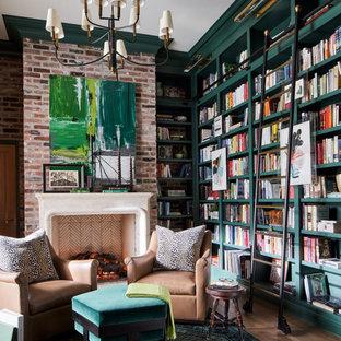 На фото: большой домашняя библиотека в стиле неоклассика (современная классика) с зелеными стенами, паркетным полом среднего тона, стандартным камином, фасадом камина из каменной кладки, отдельно стоящим рабочим столом, коричневым полом и кирпичными стенами
