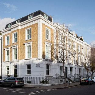 Imagen de fachada de casa pareada blanca, moderna, grande, de tres plantas, con revestimiento de ladrillo, tejado a doble faldón y tejado de teja de barro