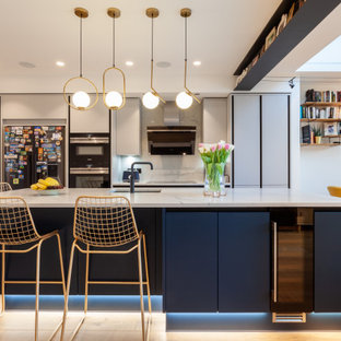 Inspiration for a contemporary kitchen in London with a built-in sink, flat-panel cabinets, grey cabinets, marble worktops, marble splashback, light hardwood flooring, an island and white worktops.