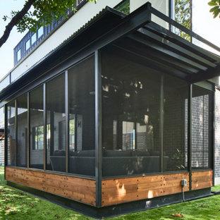 Foto di un portico design di medie dimensioni e dietro casa con un portico chiuso, pavimentazioni in cemento, un tetto a sbalzo e parapetto in metallo