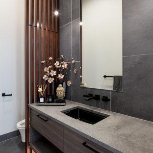 Свежая идея для дизайна: туалет среднего размера в современном стиле с плоскими фасадами, коричневыми фасадами, инсталляцией, серой плиткой, керамогранитной плиткой, белыми стенами, полом из керамогранита, врезной раковиной, столешницей из искусственного кварца, черным полом, серой столешницей, подвесной тумбой и кессонным потолком - отличное фото интерьера