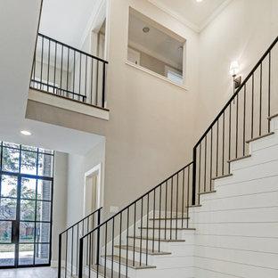 Ejemplo de escalera en U y machihembrado, tradicional renovada, grande, con escalones de madera, contrahuellas de madera pintada, barandilla de metal y machihembrado