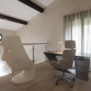Kleines Modernes Arbeitszimmer mit Arbeitsplatz, beiger Wandfarbe, gebeiztem Holzboden, freistehendem Schreibtisch, beigem Boden und freigelegten Dachbalken in Nizza