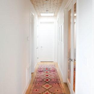 Idéer för en skandinavisk hall, med vita väggar, mellanmörkt trägolv och brunt golv