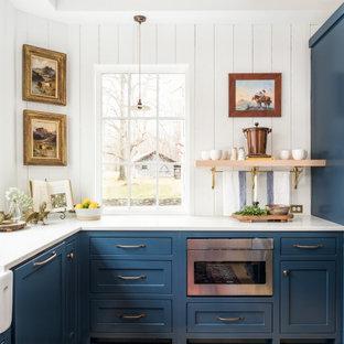 Immagine di una cucina country chiusa e di medie dimensioni con lavello stile country, ante a filo, ante blu, top in quarzo composito, paraspruzzi bianco, paraspruzzi in legno, elettrodomestici in acciaio inossidabile, parquet chiaro, pavimento giallo, top bianco e travi a vista