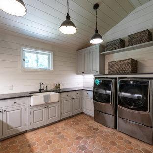 Foto på en stor funkis svarta tvättstuga enbart för tvätt, med en rustik diskho, släta luckor, grå skåp, granitbänkskiva, beige stänkskydd, beige väggar, klinkergolv i terrakotta och en tvättmaskin och torktumlare bredvid varandra