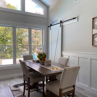 アトランタの巨大なカントリー風おしゃれなダイニングキッチン (ベージュの壁、ラミネートの床、標準型暖炉、積石の暖炉まわり、グレーの床、三角天井、羽目板の壁) の写真
