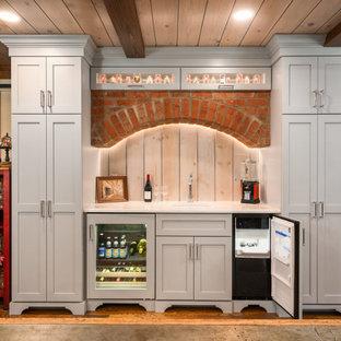 コロンバスの中くらいのトラディショナルスタイルのおしゃれなドライ バー (I型、シェーカースタイル扉のキャビネット、グレーのキャビネット、クオーツストーンカウンター、グレーのキッチンパネル、塗装板のキッチンパネル、無垢フローリング、茶色い床、白いキッチンカウンター) の写真