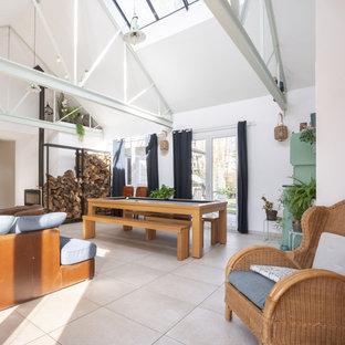 Esempio di un soggiorno industriale di medie dimensioni e aperto con sala formale, pareti bianche, pavimento con piastrelle in ceramica, nessuna TV, pavimento beige, travi a vista, carta da parati e stufa a legna
