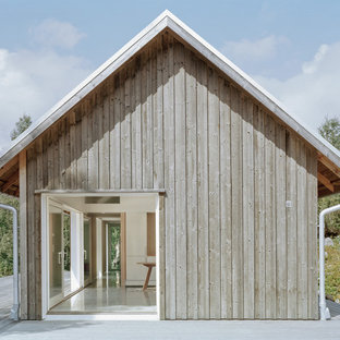 Example of a mid-sized danish gray one-story wood exterior home design in Stockholm with a clipped gable roof