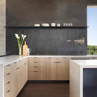 Modern inredning av ett mellanstort vit vitt kök, med en enkel diskho, släta luckor, skåp i mellenmörkt trä, bänkskiva i kvarts, stänkskydd med metallisk yta, stänkskydd i metallkakel, rostfria vitvaror, mörkt trägolv, en köksö och grått golv