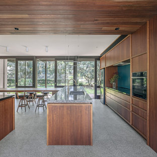 Photo of a midcentury l-shaped eat-in kitchen in Sydney with an undermount sink, flat-panel cabinets, medium wood cabinets, black appliances, with island, grey floor and grey benchtop.