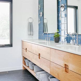 Пример оригинального дизайна: ванная комната в стиле ретро с плоскими фасадами, фасадами цвета дерева среднего тона, синей плиткой, белыми стенами, врезной раковиной, черным полом, белой столешницей, тумбой под две раковины и встроенной тумбой
