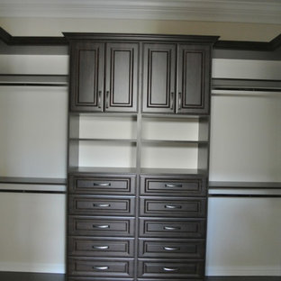 Design ideas for a large traditional gender neutral walk-in wardrobe in Miami with raised-panel cabinets, dark wood cabinets and travertine flooring.