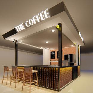 Immagine di un piccolo angolo bar senza lavandino moderno con ante a filo, ante nere, top in granito e top arancione