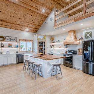 ヒューストンの中くらいのカントリー風おしゃれなキッチン (エプロンフロントシンク、シェーカースタイル扉のキャビネット、白いキャビネット、木材カウンター、白いキッチンパネル、塗装板のキッチンパネル、シルバーの調理設備、クッションフロア、ベージュの床、ベージュのキッチンカウンター、板張り天井) の写真