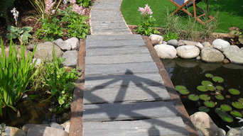 Slatewood beams and footbridge over a water feature