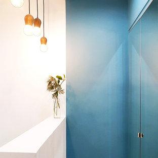 Exemple d'une armoire encastrée tendance de taille moyenne avec un placard à porte affleurante, sol en stratifié et un plafond en poutres apparentes.