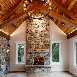 Идея дизайна: большая хозяйская спальня в стиле рустика с серыми стенами, паркетным полом среднего тона, стандартным камином, фасадом камина из камня, серым полом и потолком из вагонки