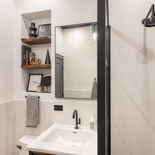 На фото: маленькая ванная комната в стиле модернизм с фасадами островного типа, коричневыми фасадами, душем в нише, унитазом-моноблоком, белой плиткой, керамогранитной плиткой, белыми стенами, полом из керамогранита, монолитной раковиной, столешницей из искусственного камня, черным полом, открытым душем, белой столешницей, нишей, тумбой под одну раковину, напольной тумбой, потолком с обоями и панелями на стенах