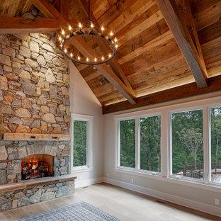 他の地域の広いラスティックスタイルのおしゃれな主寝室 (グレーの壁、無垢フローリング、標準型暖炉、石材の暖炉まわり、グレーの床、塗装板張りの天井)