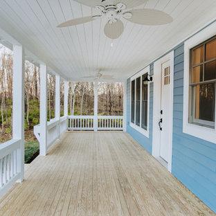 Ispirazione per un ampio portico stile americano davanti casa con pedane, un tetto a sbalzo e parapetto in legno
