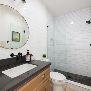 Photo of a transitional 3/4 bathroom in Orange County with shaker cabinets, medium wood cabinets, an alcove shower, a two-piece toilet, subway tile, white walls, wood-look tile, an undermount sink, engineered quartz benchtops, brown floor, a hinged shower door, black benchtops, a single vanity, a built-in vanity and planked wall panelling.