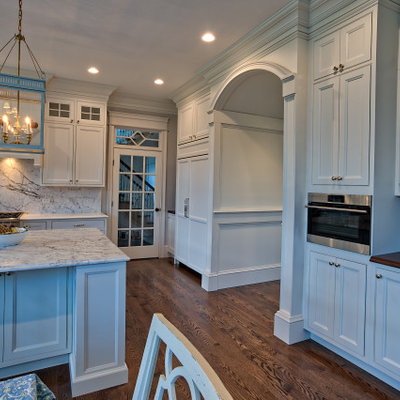 Eat-in kitchen - large traditional u-shaped medium tone wood floor and brown floor eat-in kitchen idea in Philadelphia with a farmhouse sink, beaded inset cabinets, white cabinets, quartz countertops, white backsplash, quartz backsplash, stainless steel appliances, an island and white countertops