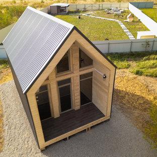 Стильный дизайн: маленький, одноэтажный, синий мини дом в современном стиле с облицовкой из металла, двускатной крышей и синей крышей - последний тренд