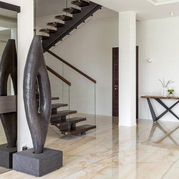 Фойе с лестницей просторного загородного дома.