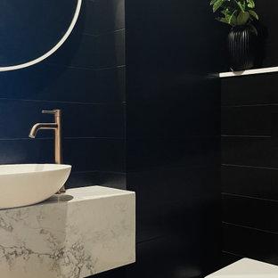 Источник вдохновения для домашнего уюта: маленький туалет в современном стиле с белыми фасадами, инсталляцией, черной плиткой, черными стенами, светлым паркетным полом, раковиной с пьедесталом, мраморной столешницей, белой столешницей, подвесной тумбой и стенами из вагонки