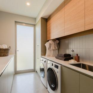 Foto di una grande lavanderia multiuso minimal con lavello integrato, ante in legno chiaro, top in laminato, paraspruzzi grigio, paraspruzzi con piastrelle diamantate, lavatrice e asciugatrice affiancate, pavimento bianco e top bianco