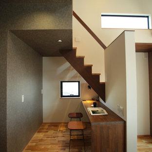 Inredning av ett modernt hemmabibliotek, med grå väggar, ljust trägolv, ett inbyggt skrivbord och beiget golv