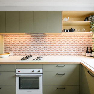 This is an example of a small scandinavian l-shaped separate kitchen in Melbourne with a double-bowl sink, flat-panel cabinets, green cabinets, laminate benchtops, multi-coloured splashback, ceramic splashback, white appliances, ceramic floors, beige floor and white benchtop.