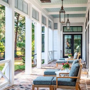 Ispirazione per un portico country dietro casa con pavimentazioni in mattoni, un tetto a sbalzo e parapetto in legno