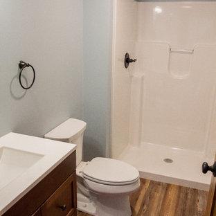 Diseño de cuarto de baño infantil, de estilo americano, pequeño, con armarios con paneles con relieve, puertas de armario de madera oscura, ducha empotrada, sanitario de dos piezas, paredes azules, suelo laminado, lavabo integrado, encimera de acrílico, suelo marrón y ducha abierta