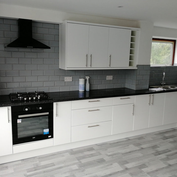 Inspiration for a large modern grey and white kitchen in Hampshire with a double-bowl sink, flat-panel cabinets, white cabinets, laminate countertops, grey splashback, ceramic splashback, black applia
