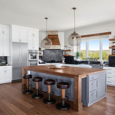 Example of a large beach style l-shaped medium tone wood floor and brown floor eat-in kitchen design in Austin with a farmhouse sink, shaker cabinets, gray cabinets, black backsplash, stone slab backsplash, stainless steel appliances, an island, black countertops and wood countertops