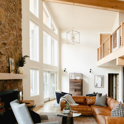 Large mountain style open concept light wood floor living room photo in Denver with white walls