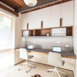 Kleines Retro Arbeitszimmer mit weißer Wandfarbe, Teppichboden, Einbau-Schreibtisch, beigem Boden und freigelegten Dachbalken in Melbourne