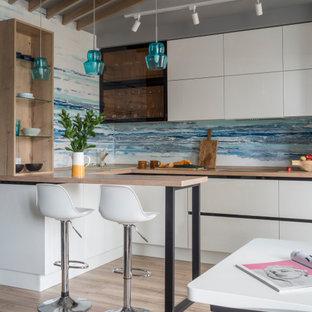 Свежая идея для дизайна: п-образная кухня в современном стиле с плоскими фасадами, белыми фасадами, деревянной столешницей, синим фартуком, светлым паркетным полом, полуостровом, бежевым полом, бежевой столешницей, балками на потолке и сводчатым потолком - отличное фото интерьера